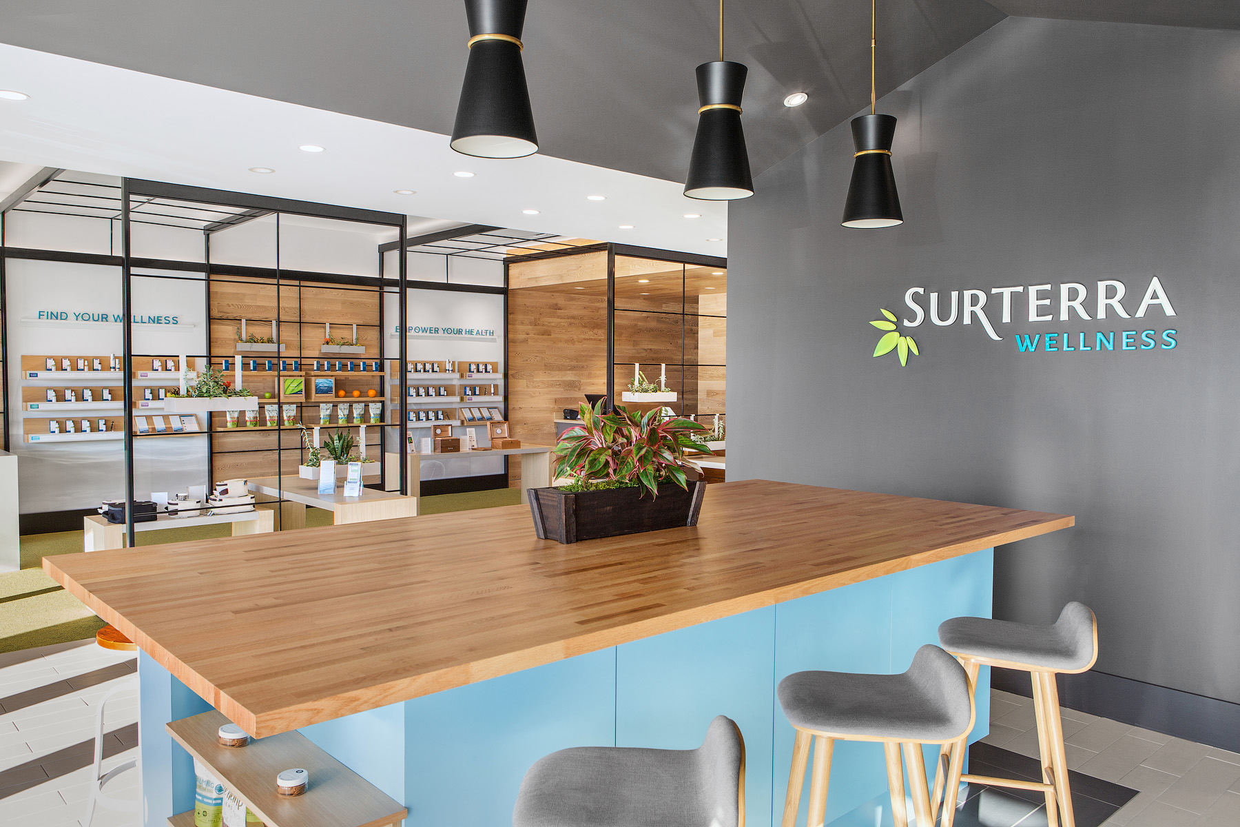 Surterra kitchen with wood-top island and grey wall behind featuring Surterra logo