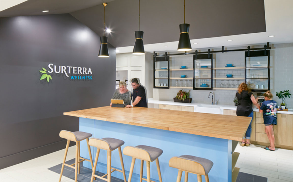 Surterra kitchen with island, bar stools, sink, and salespeople and customers talking and browsing