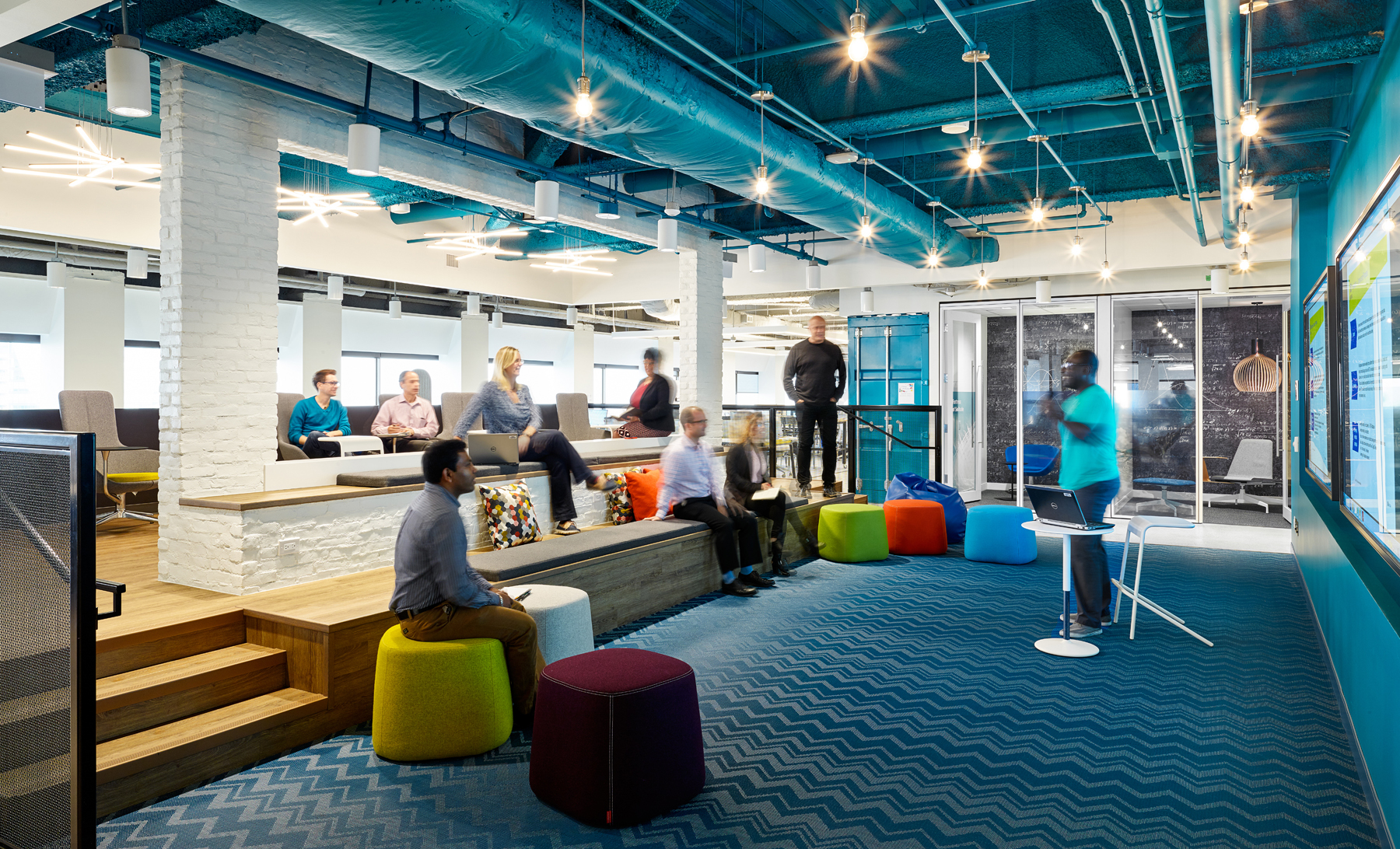 AVIVA Digital Garage meeting area with blue carpeting, colourful poufs, and open ceiling