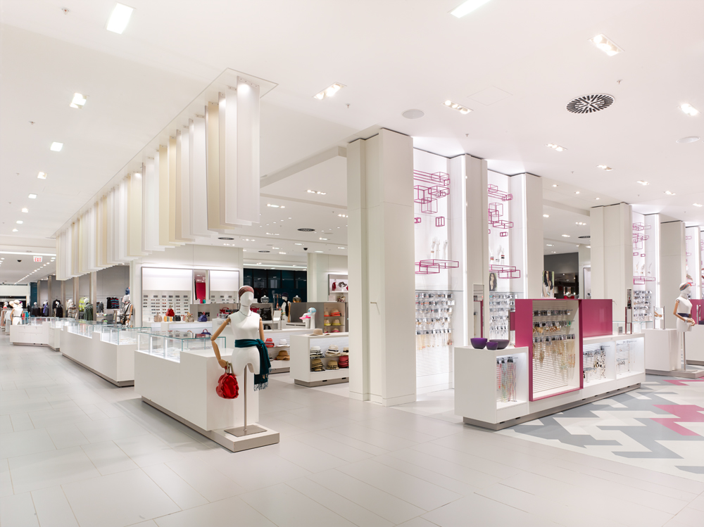 Simons accessories department with white floors, ceiling, and display cases, and pink accents