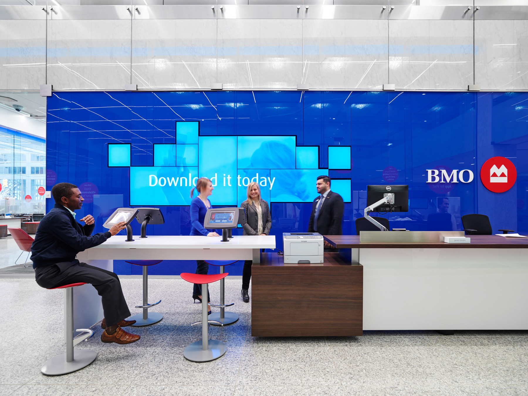 BMO collaboration area with desks and computers in front of blue wall with digital screens and BMO logo
