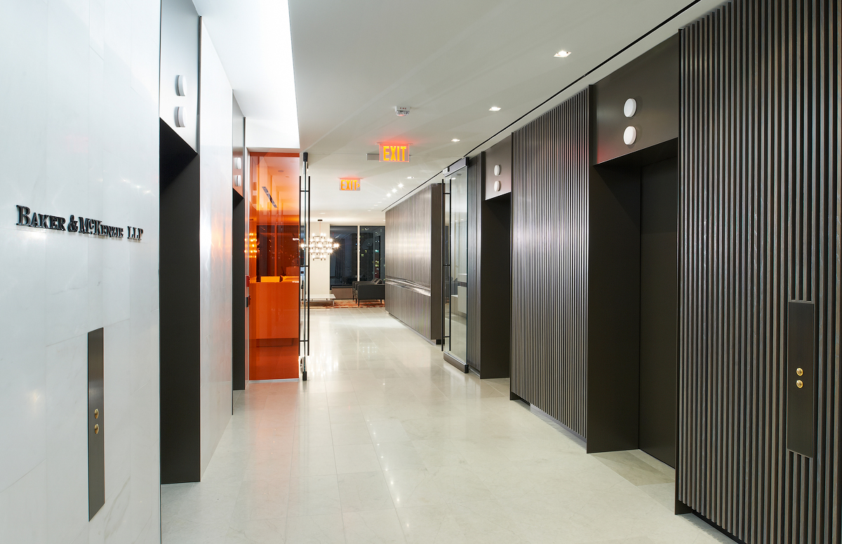 Baker & McKenzie elevator lobby with orange glass wall and marble floors
