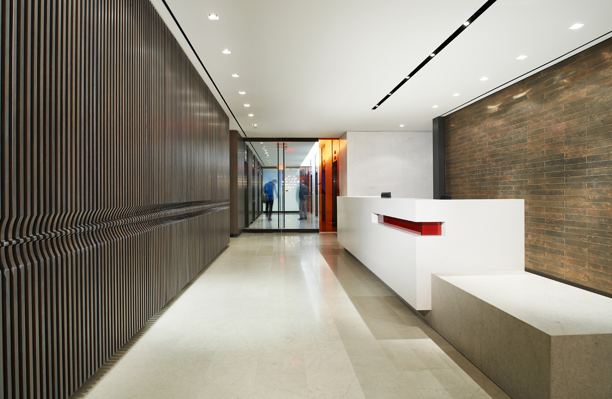 Baker & McKenzie reception with stone wall, white desk, and marble floors