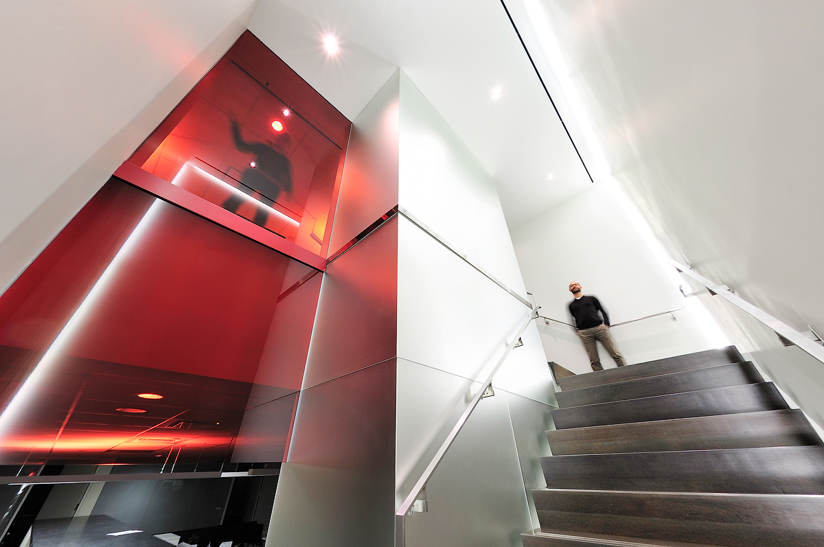 Baker & McKenzie man standing at top of stairs, next to elevator made of red translucent glass