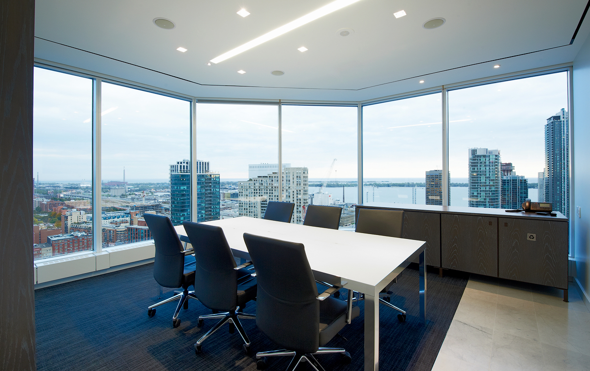 Baker & McKenzie meeting room in centre, in front of large windows showing view of tall buildings