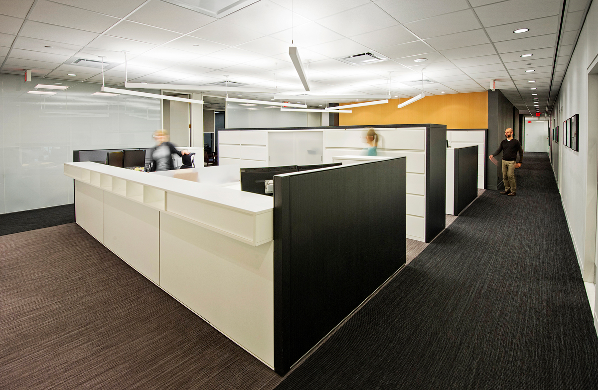 Baker & McKenzie workstations with white and dark brown walls, and gold accent wall in background