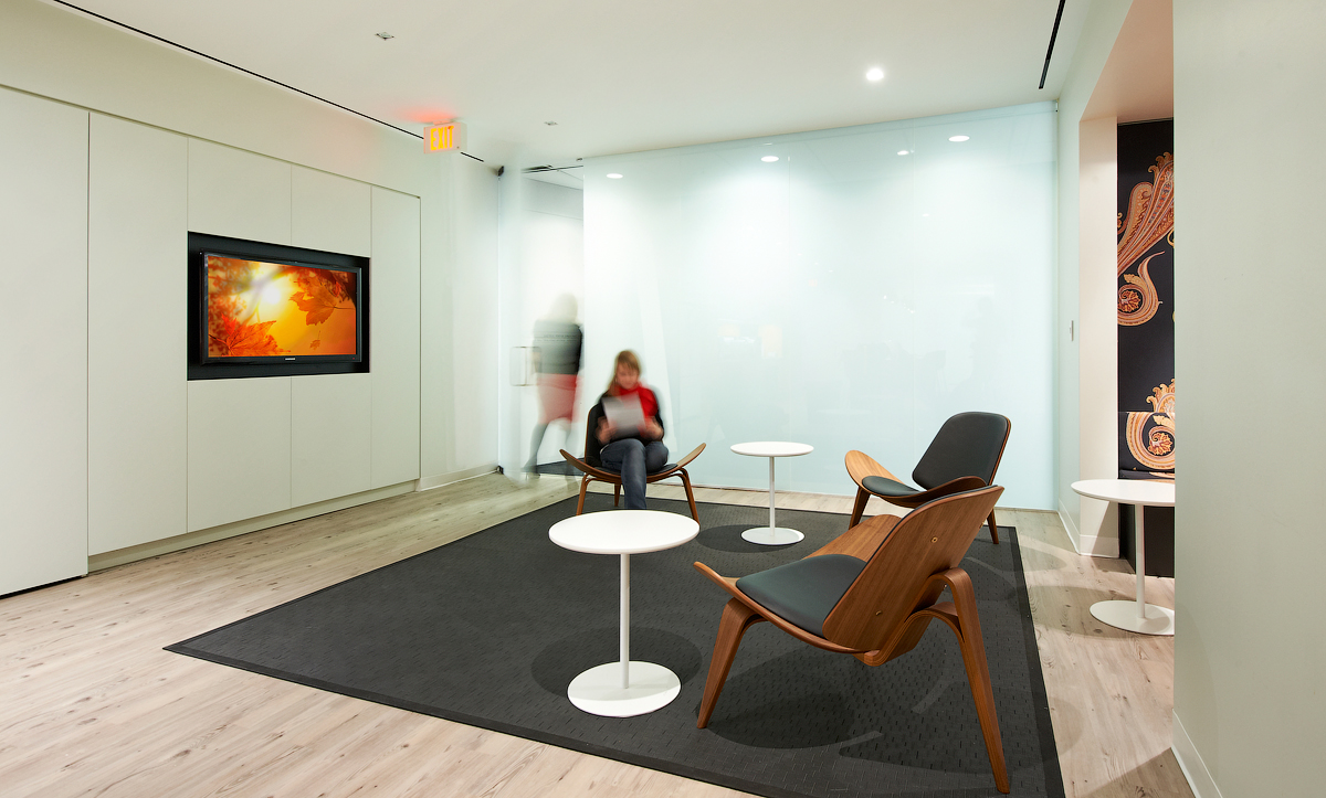 Baker & McKenzie seating area with dark grey rug, wood arm chairs, and white walls
