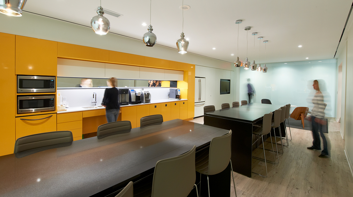 Baker & McKenzie yellow kitchen with two bar height tables and stools