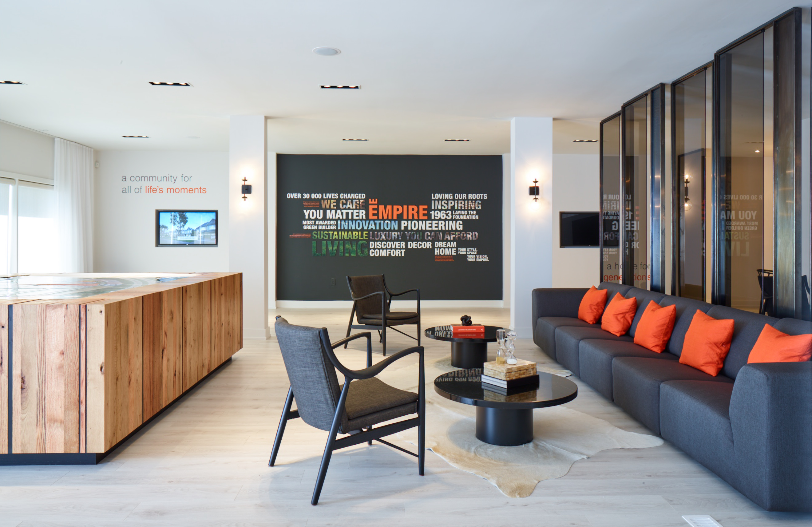 Empire Legacy reception area with brown wood desk, dark grey sofa, and graphic wall with inspirational text collage