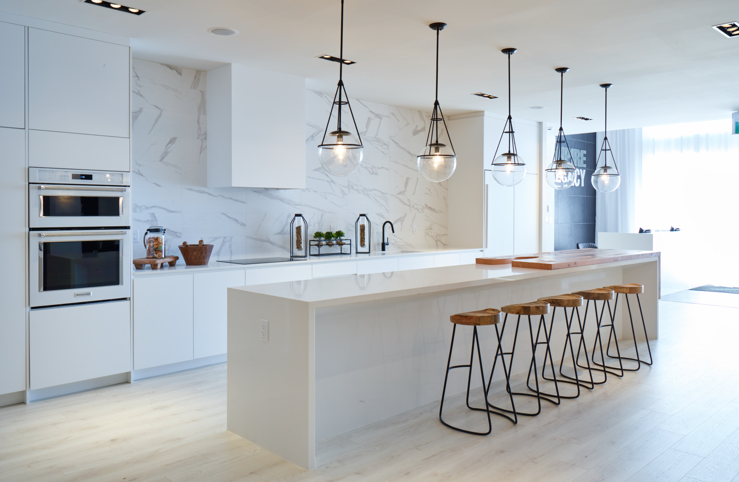 Empire Thorold white kitchen with white marble backsplash, metal and wood stools, and black metal pendant lights