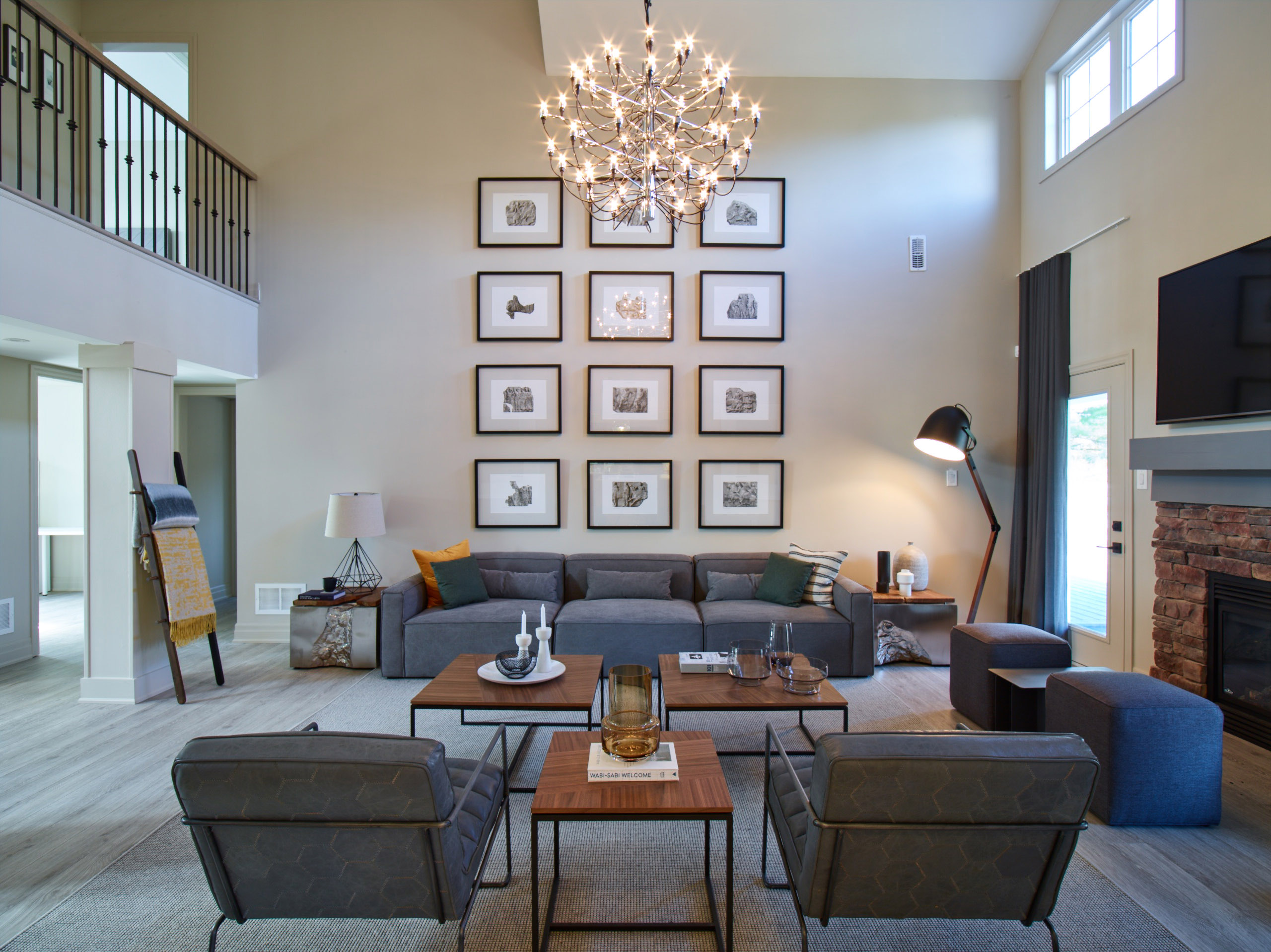 Oak Bay living room with high ceiling, gallery wall with black frames, grey sofa and chairs, and wood tables