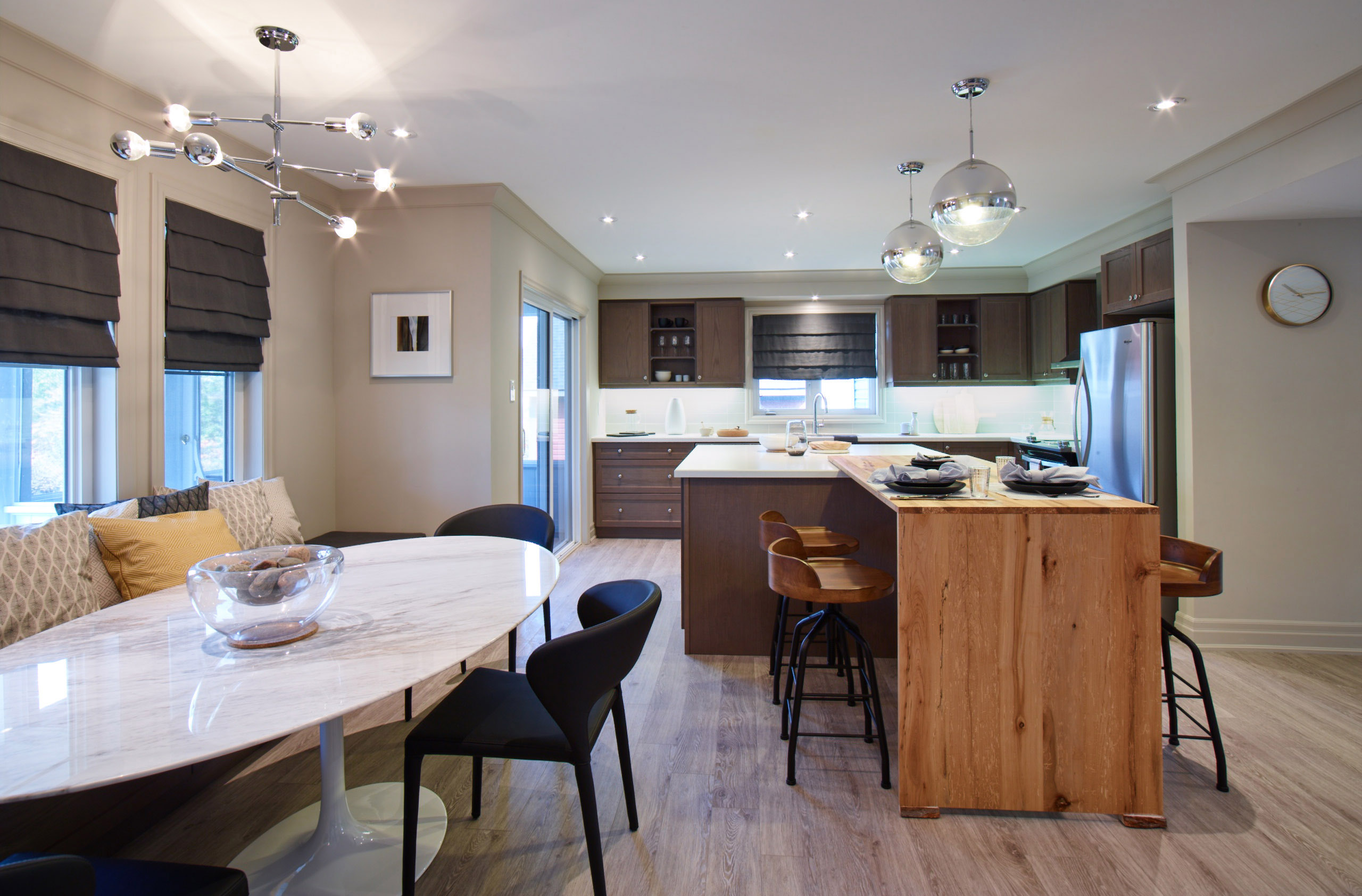 Oak Bay kitchen with dark brown cabinets, natural wood island, and white marble table