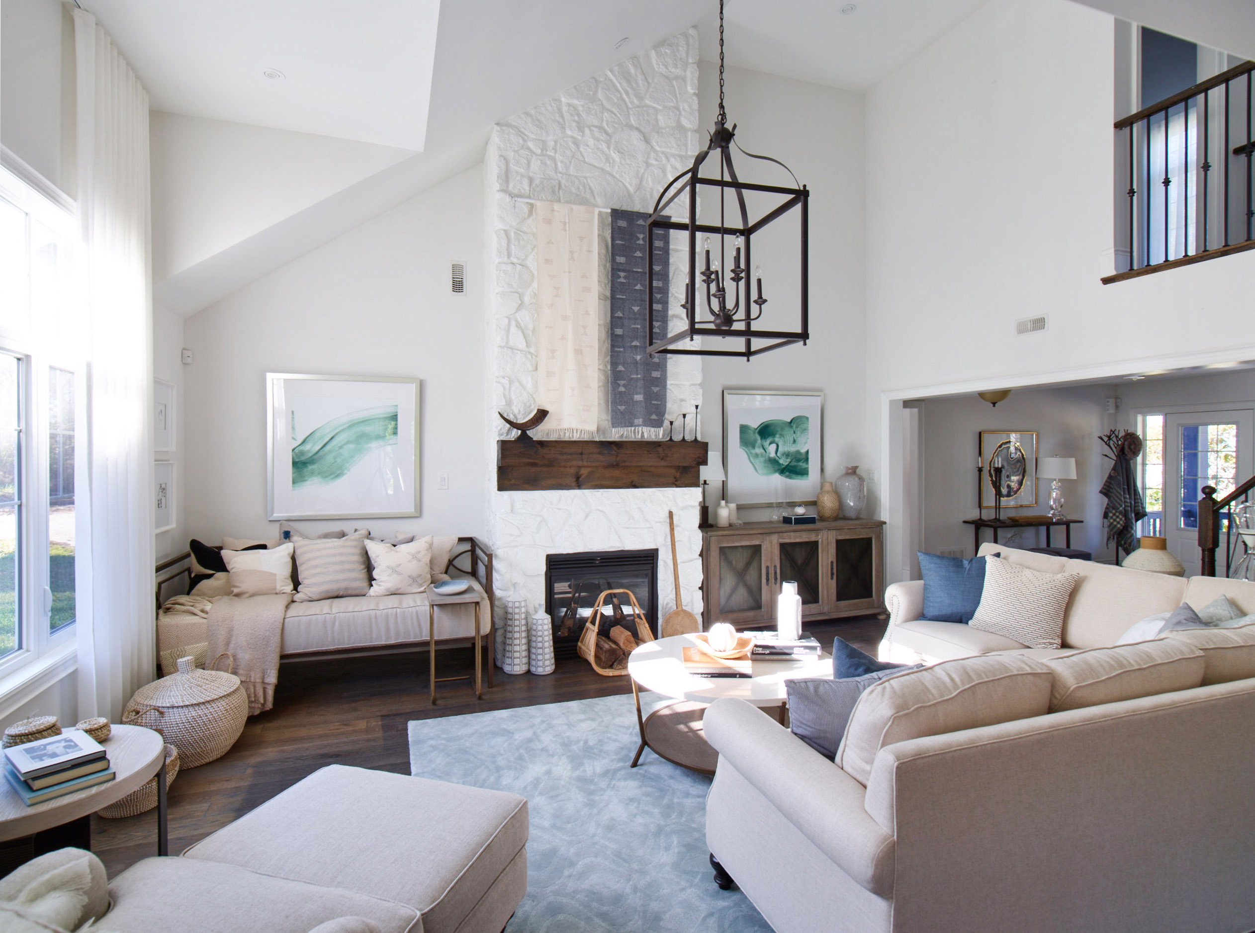 Oak Bay den with high ceilings, white brick fireplace, and large black metal lantern pendant