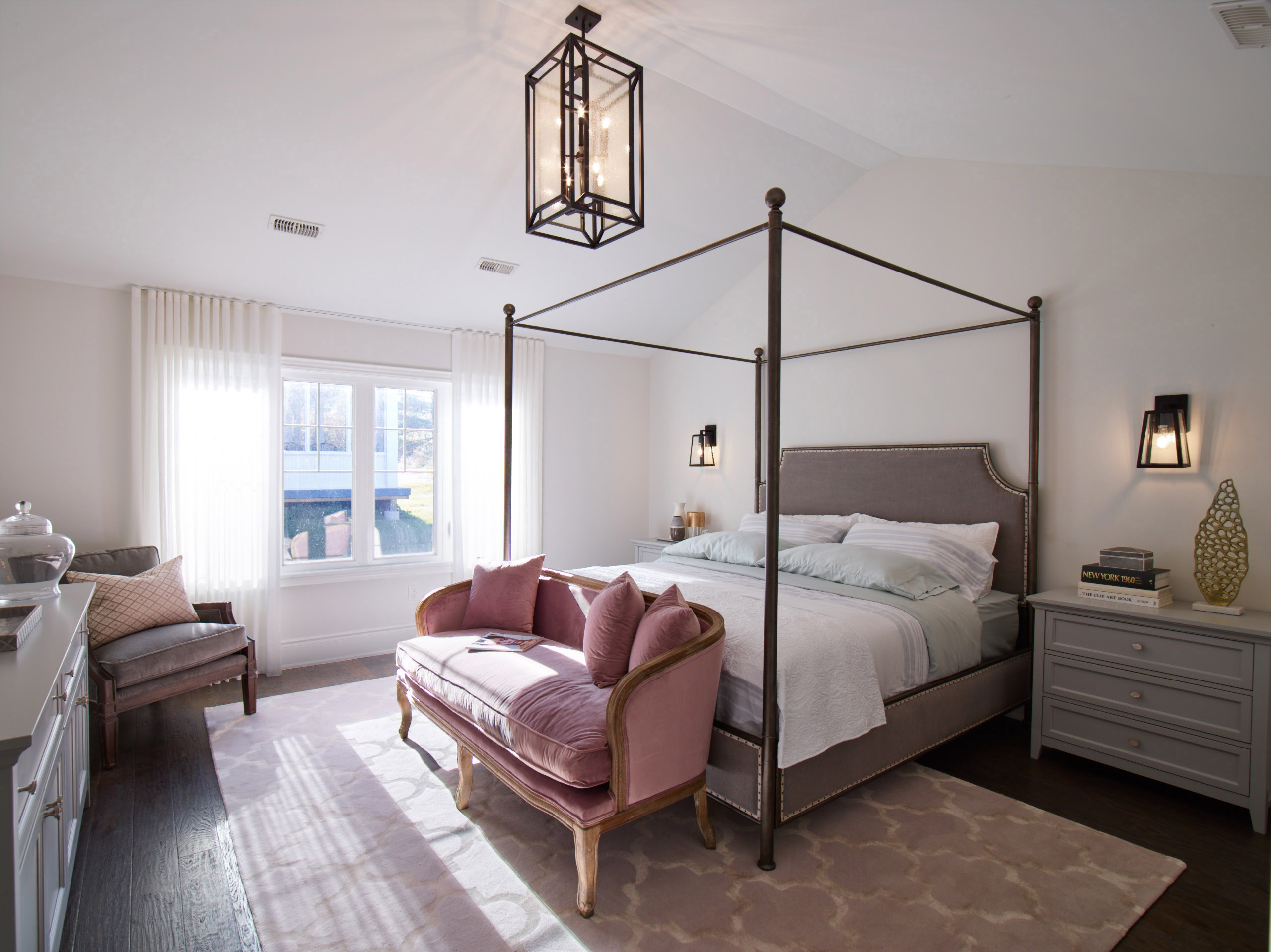 Oak Bay bedroom with four poster bed, pink velvet settee, and white and grey accents