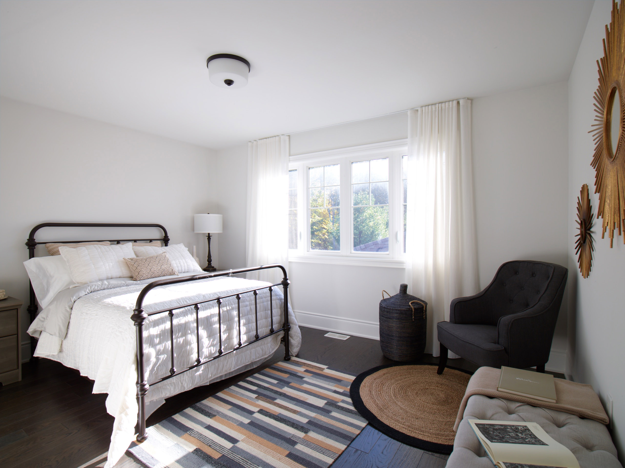 Oak Bay white bedroom with vintage black iron bed, and geometric patterned rug