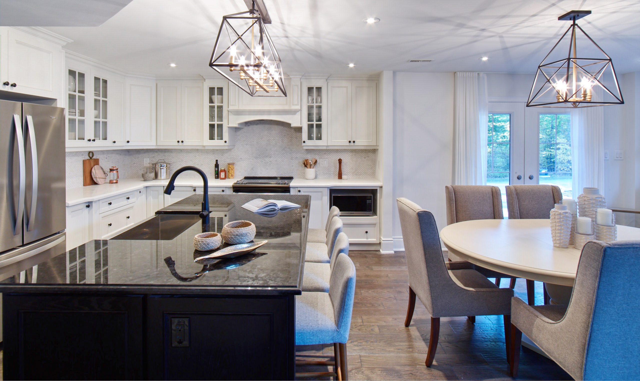 Oak Bay white kitchen with black island, round table, and modern lantern pendant lights
