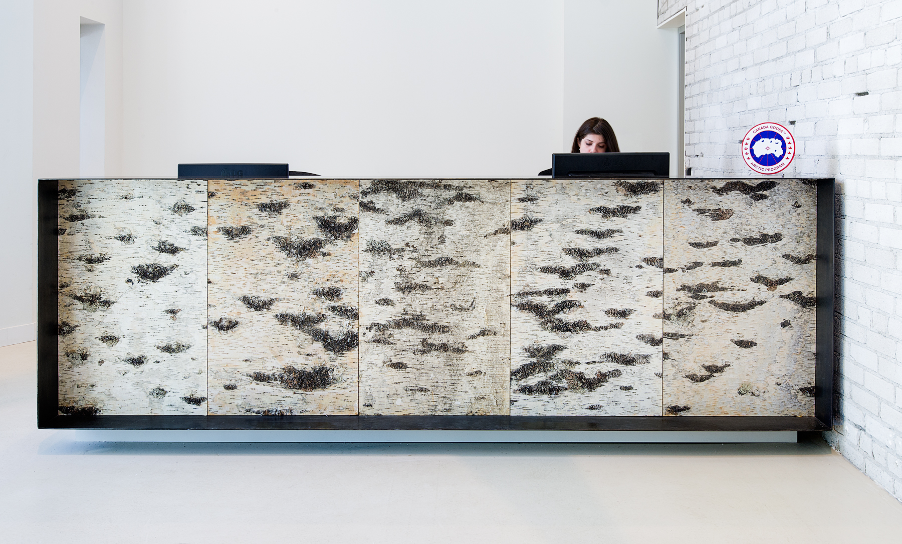 Canada Goose reception desk covered in birch bark, sitting in front of white brick walls with company logo