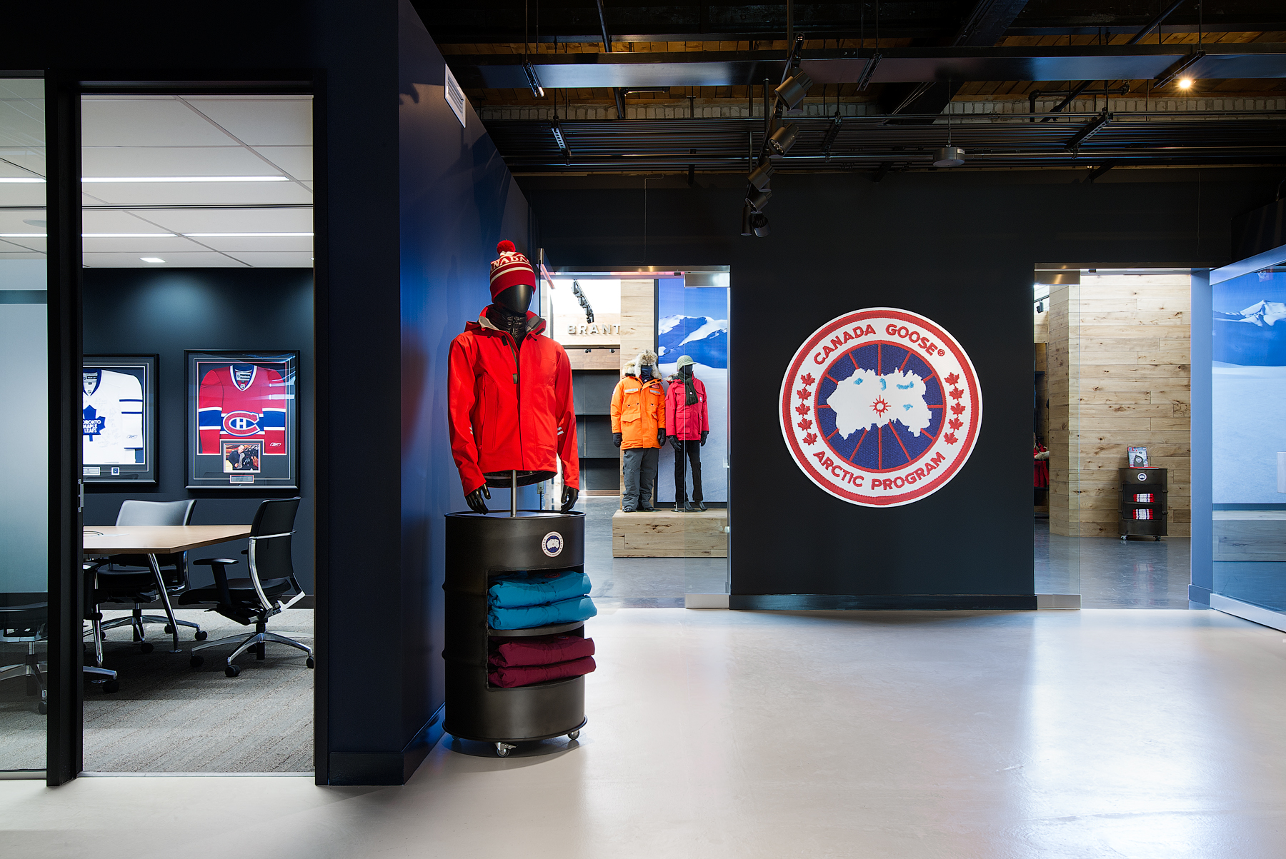 Canada Goose open area with black walls, Canada Goose logo on wall, and mannequin wearing red coat