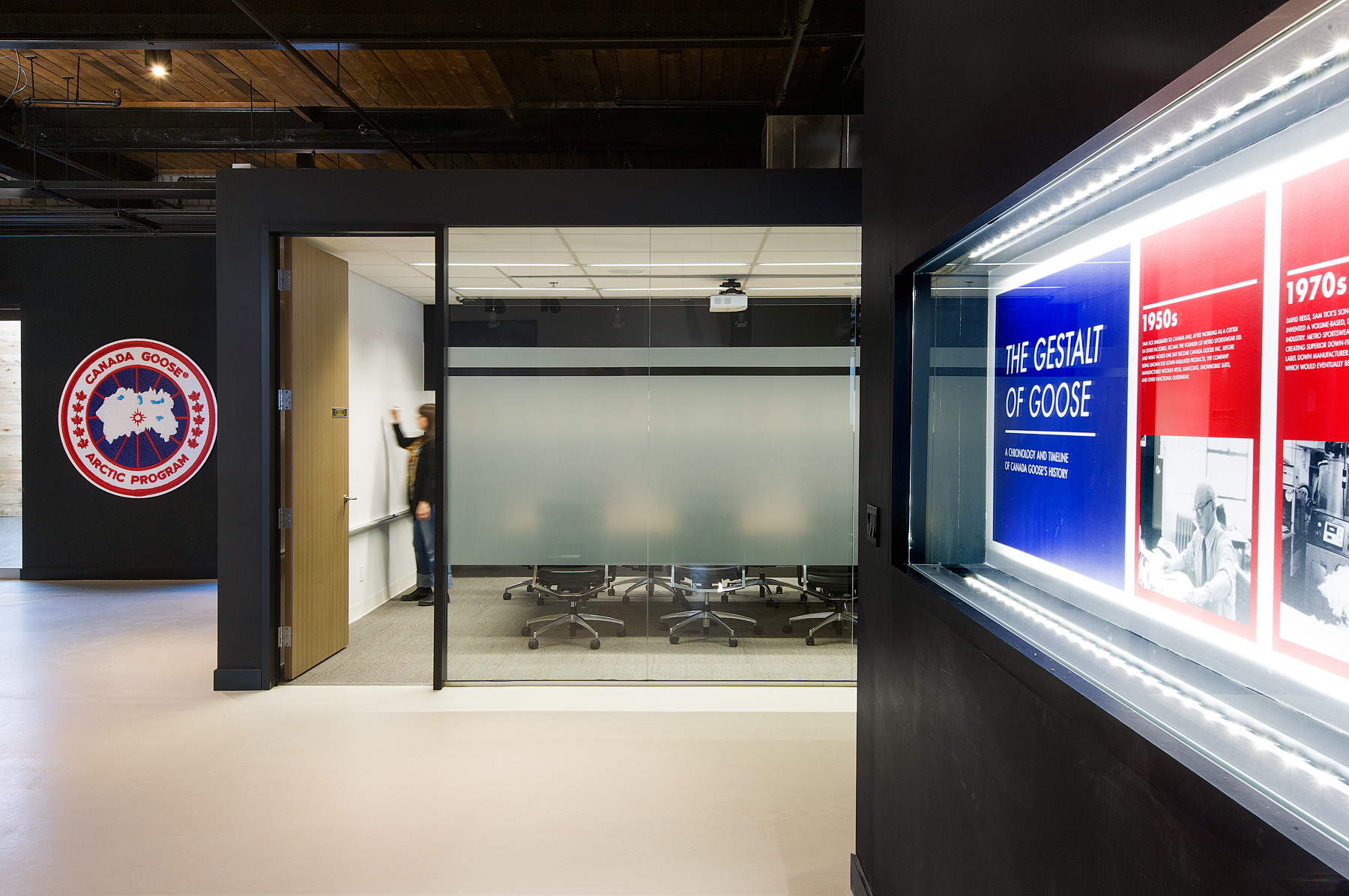 Canada Goose hallway with black walls featuring company logo, and view into meeting room with glass walls