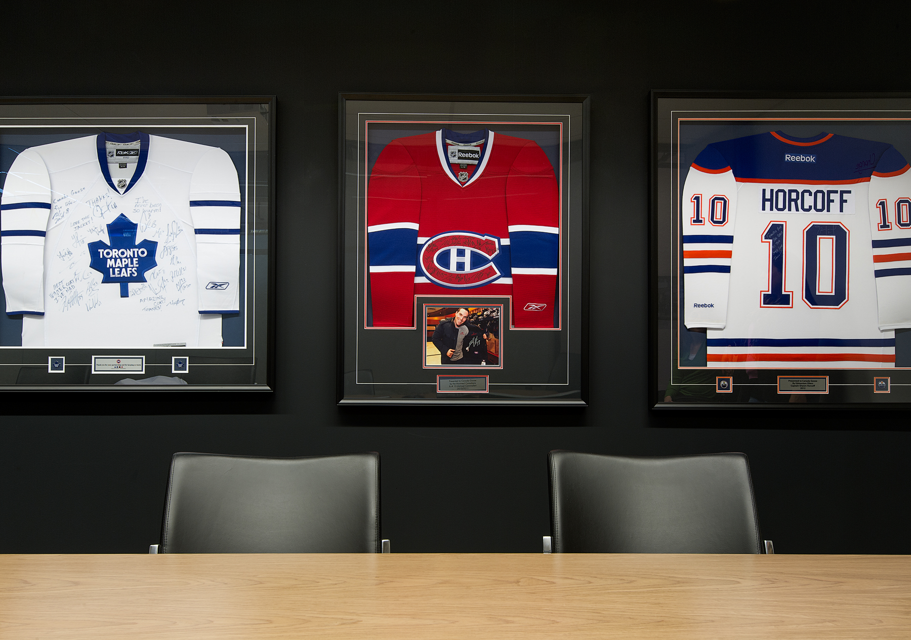 Canada Goose close up of black wall displaying three framed hockey jerseys
