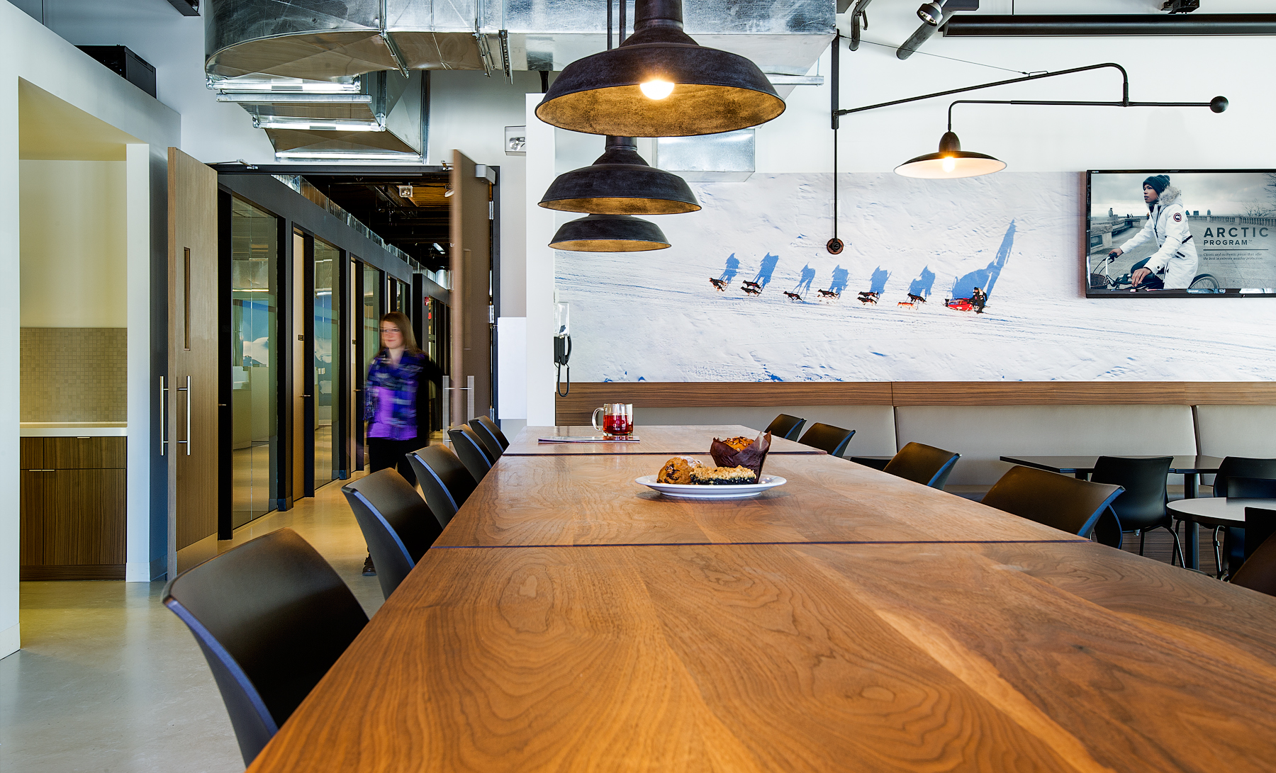 Canada Goose meeting space with long wood table, industrial lights, and white walls with winter-themed graphics