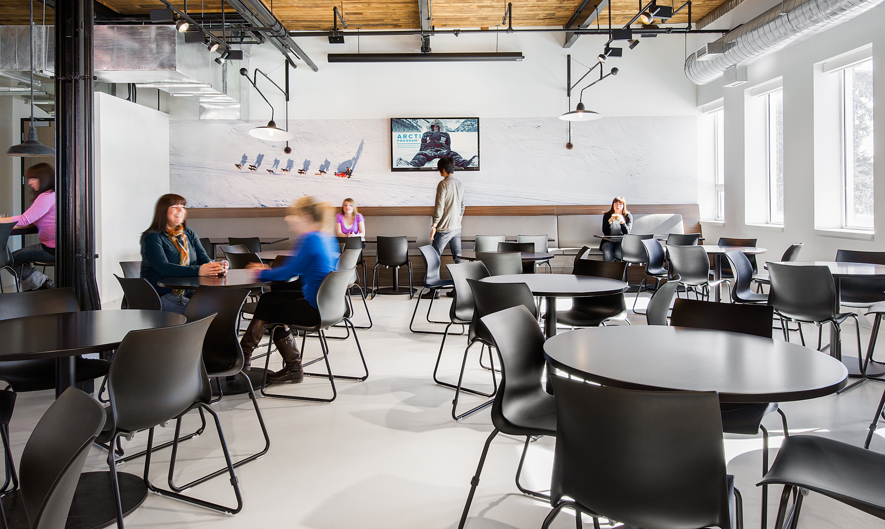 Canada Goose lunchroom with white walls, industrial lighting, open ceiling, and black tables and chairs