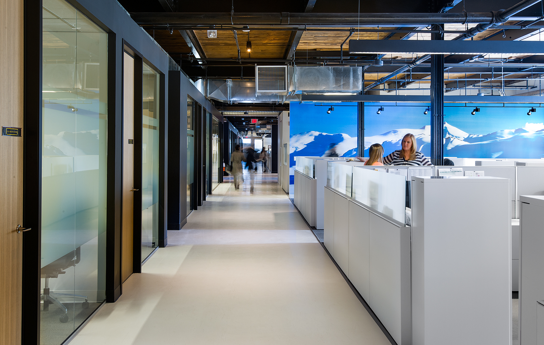 Canada Goose hallway with workstations on right and meeting rooms on left, and wall featuring mountain view mural