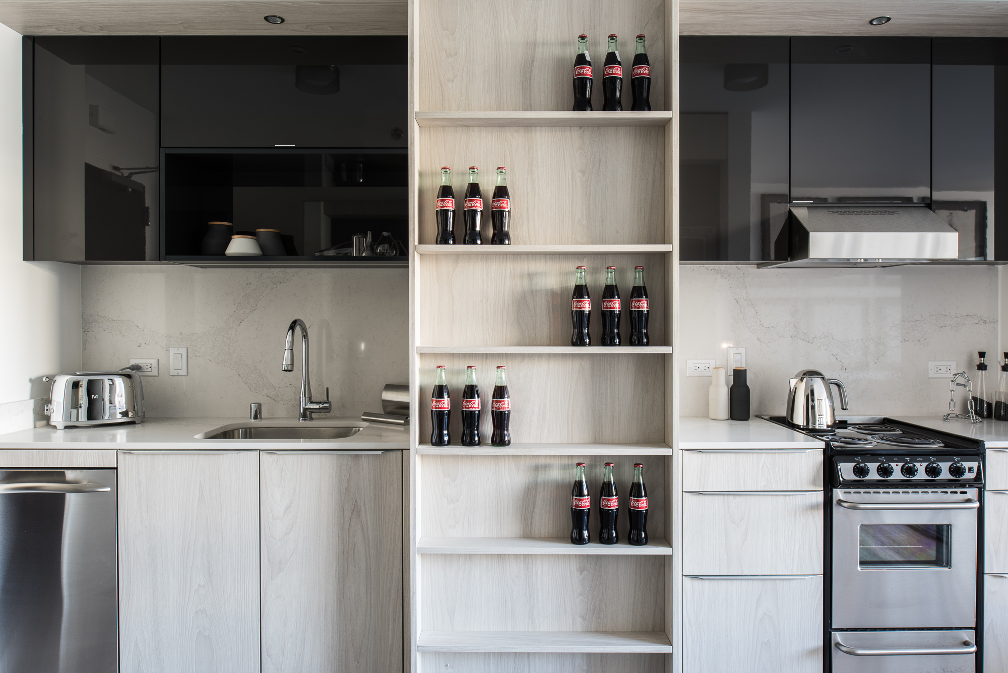 Trinity San Francisco kitchen detail of coke bottles on light wood shelving with glossy black cabinets above