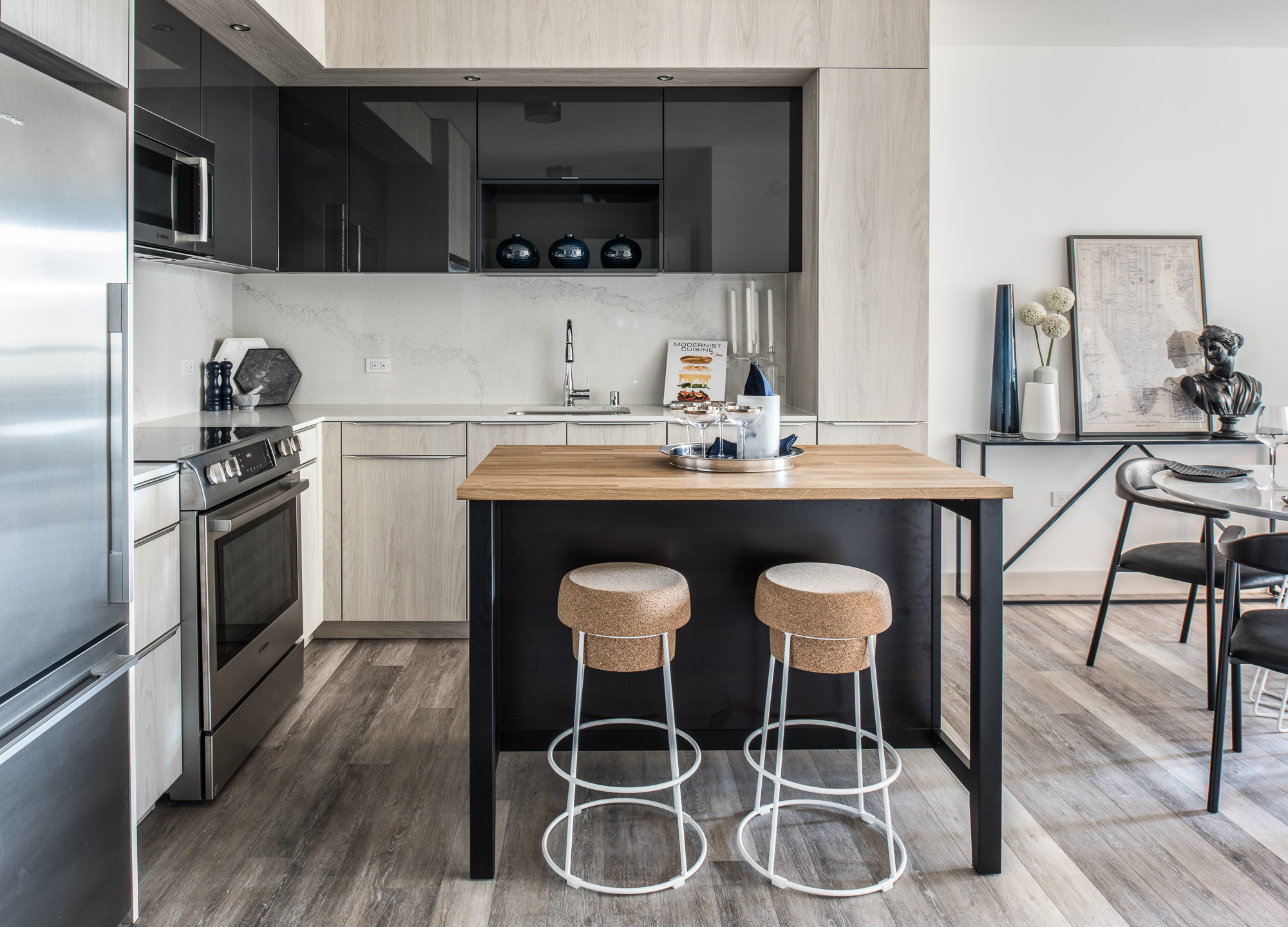 Trinity San Francisco kitchen with light wood cabinets and floors and black metal island with white metal stools