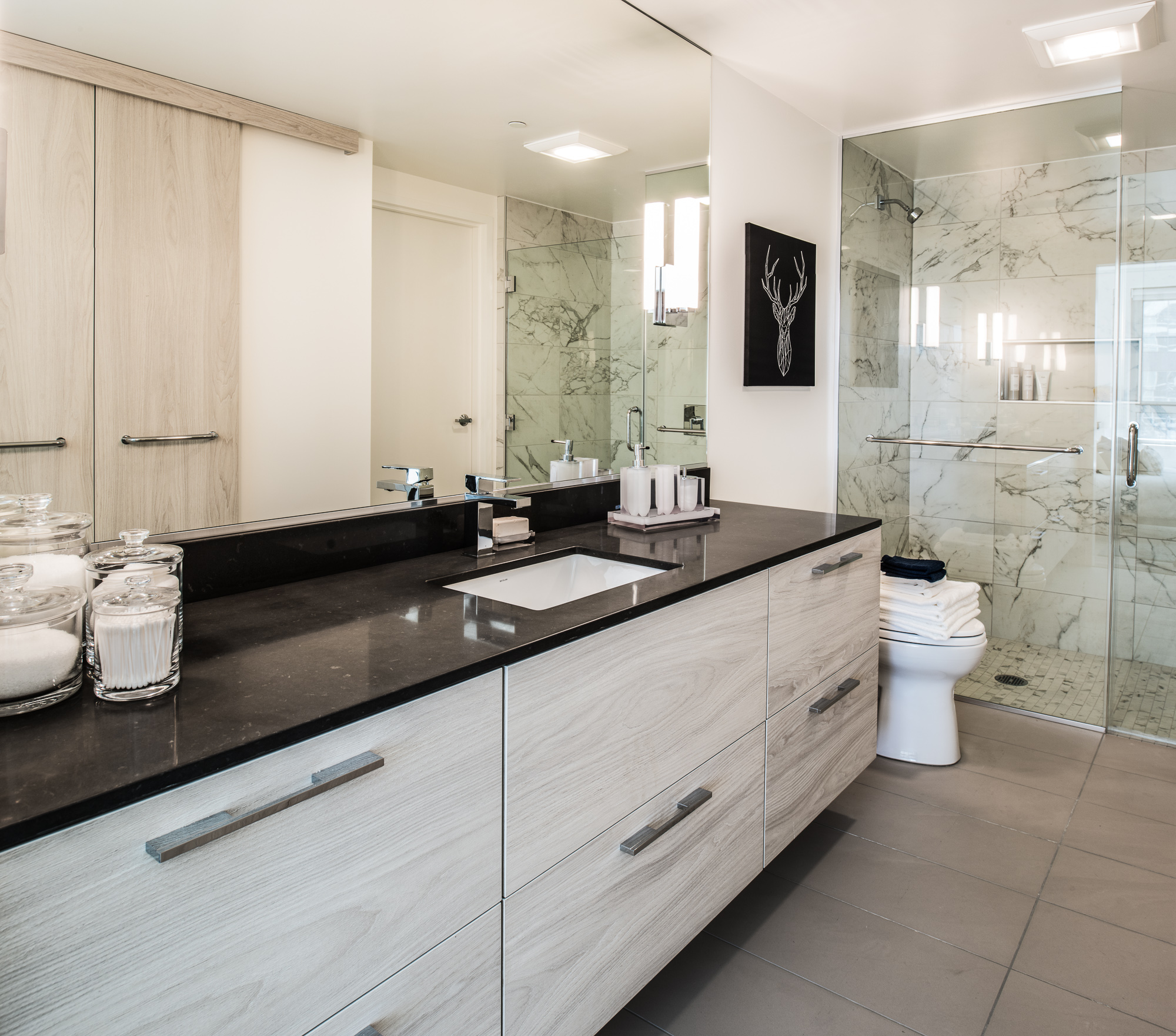 Trinity San Francisco bathroom with light wood vanity, black stone countertop, and white marble shower