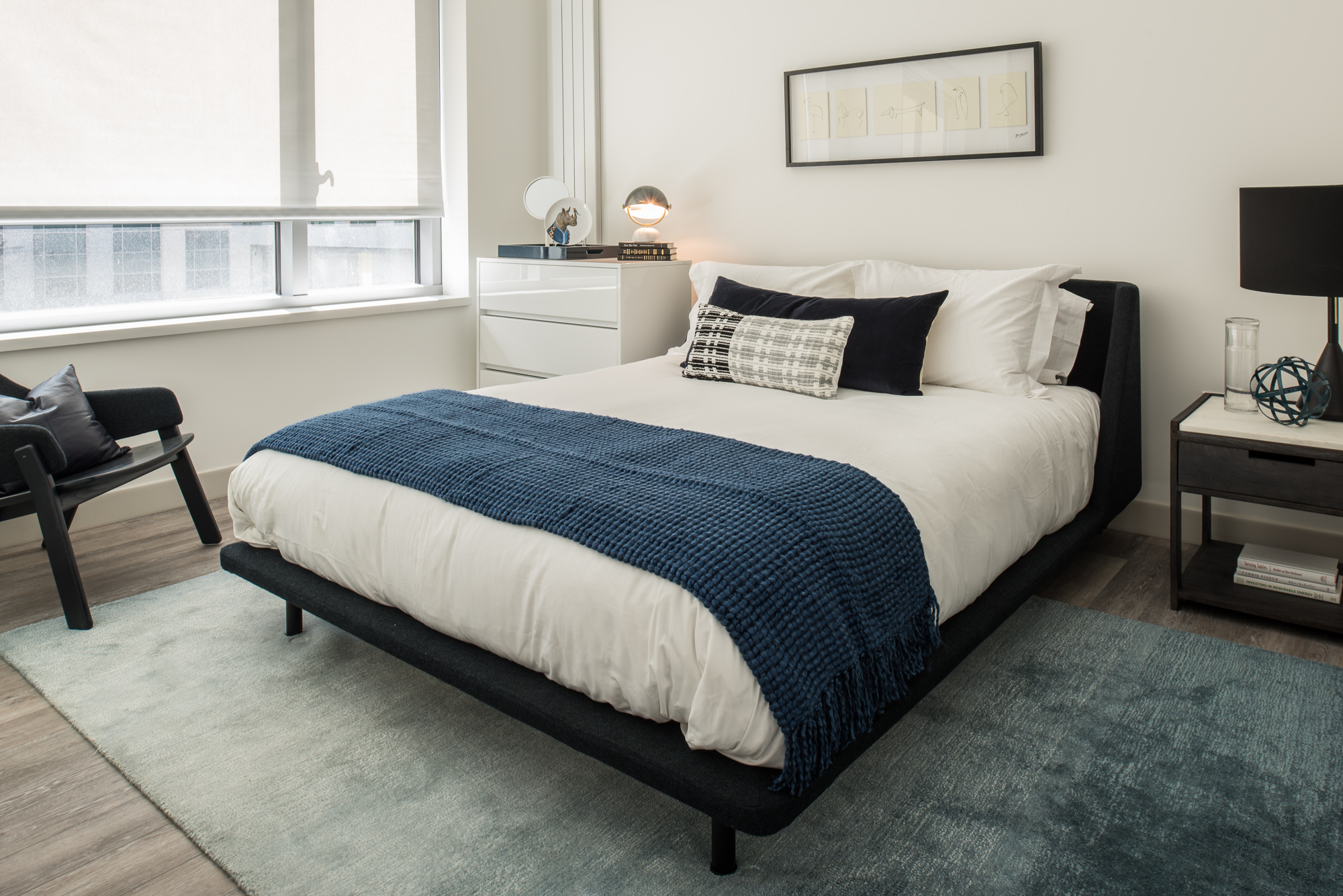 Trinity San Francisco bedroom with black bed and chair, white dresser and bedding, and navy throw blanket