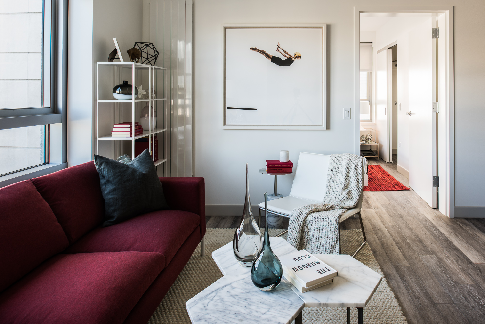 Trinity San Francisco living room with red sofa, white marble tables, and artwork with diver