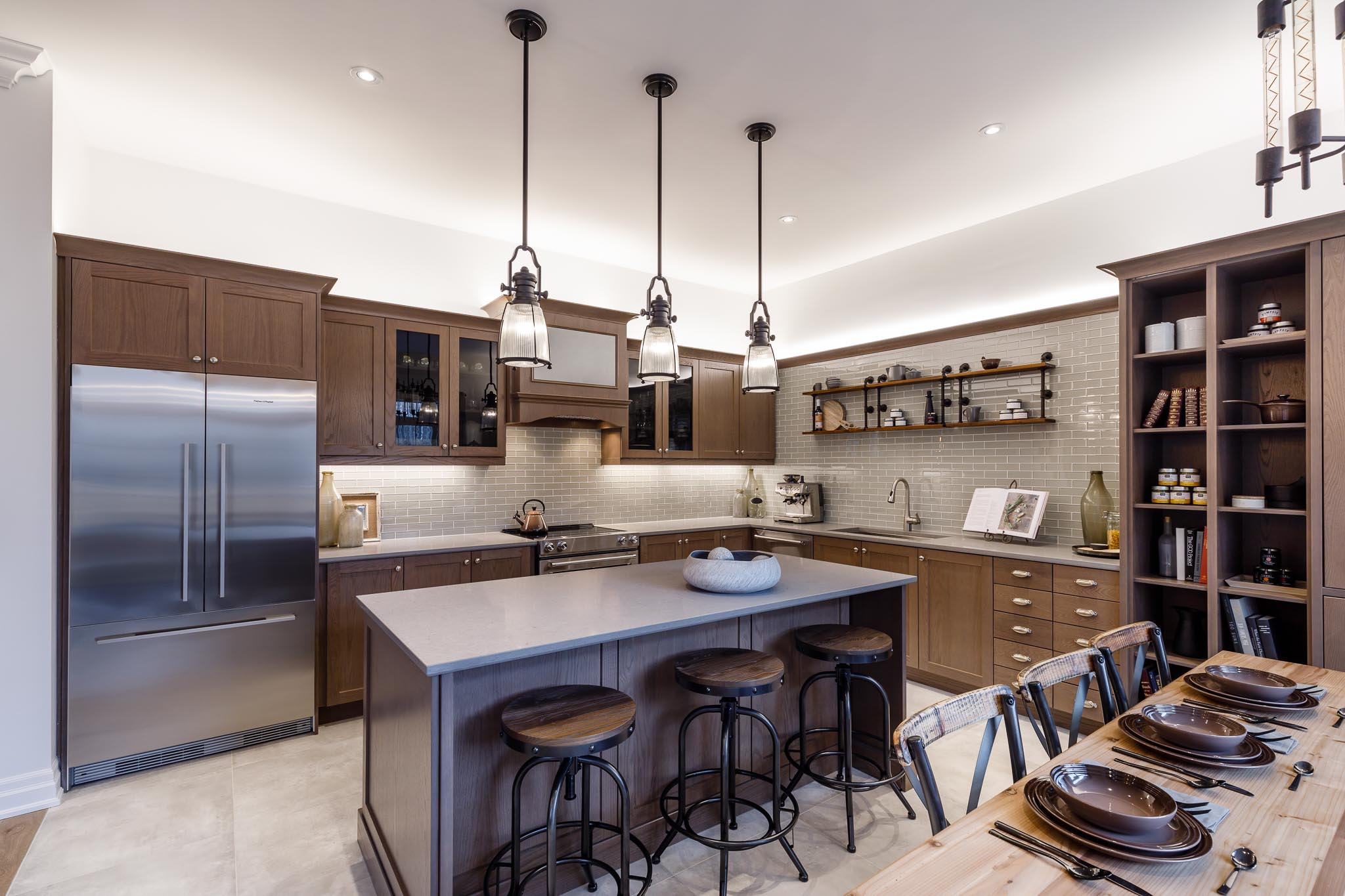 Great Gulf Westfield kitchen with brown cabinetry and industrial lighting and stools