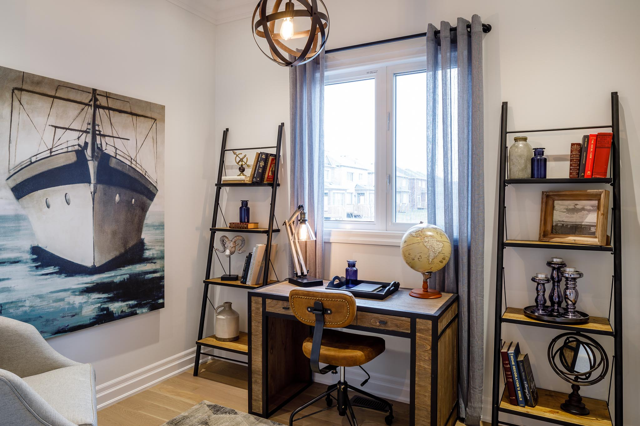 Great Gulf Westfield bedroom with wood desk against window, ladder shelving, and artwork with boat