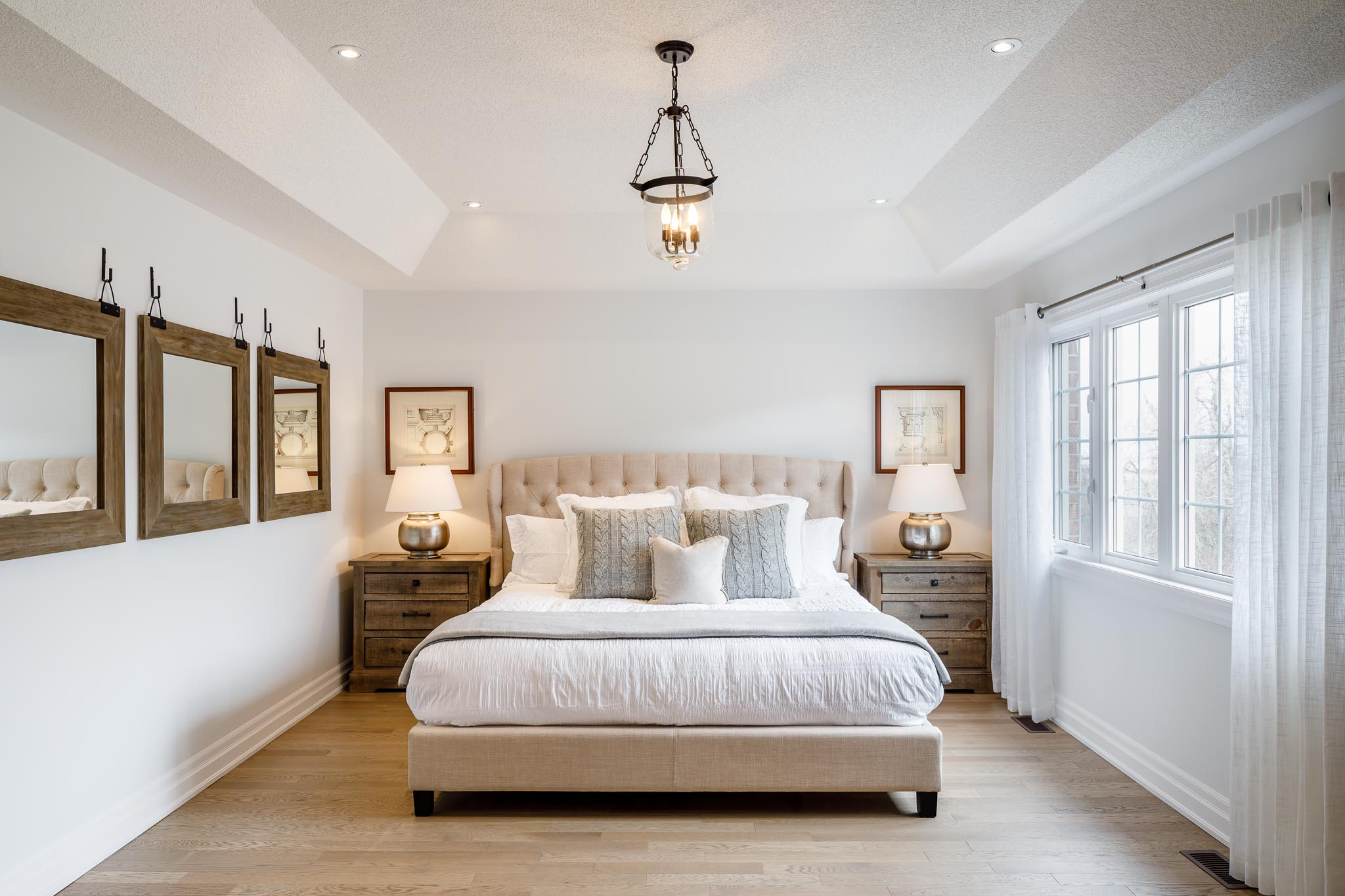 Great Gulf Westfield master bedroom with upholstered bed, white bedding, white walls, and light wood accents