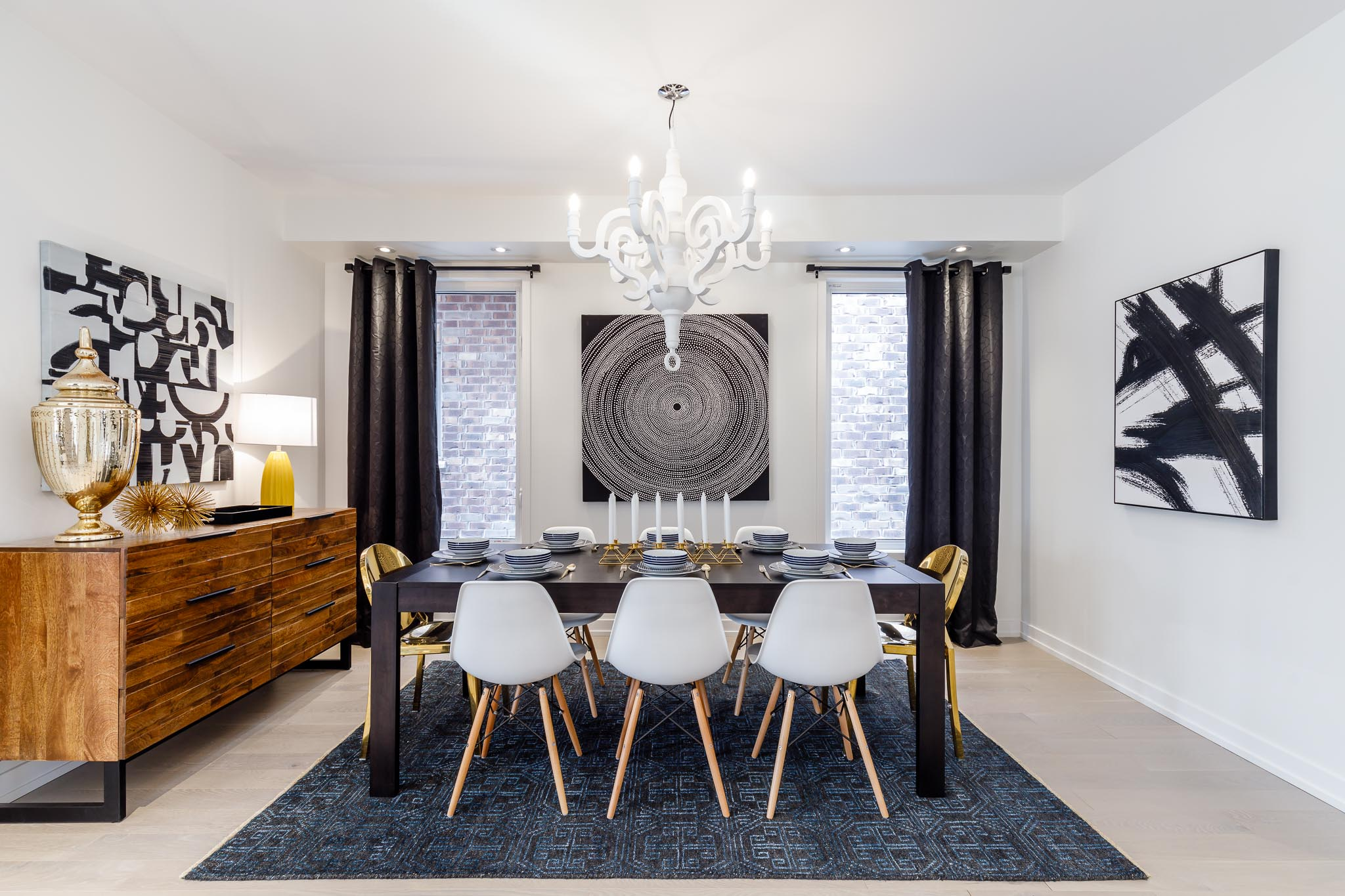 Great Gulf Westfield dining room with black table, white chairs, black and white artwork, and white chandelier