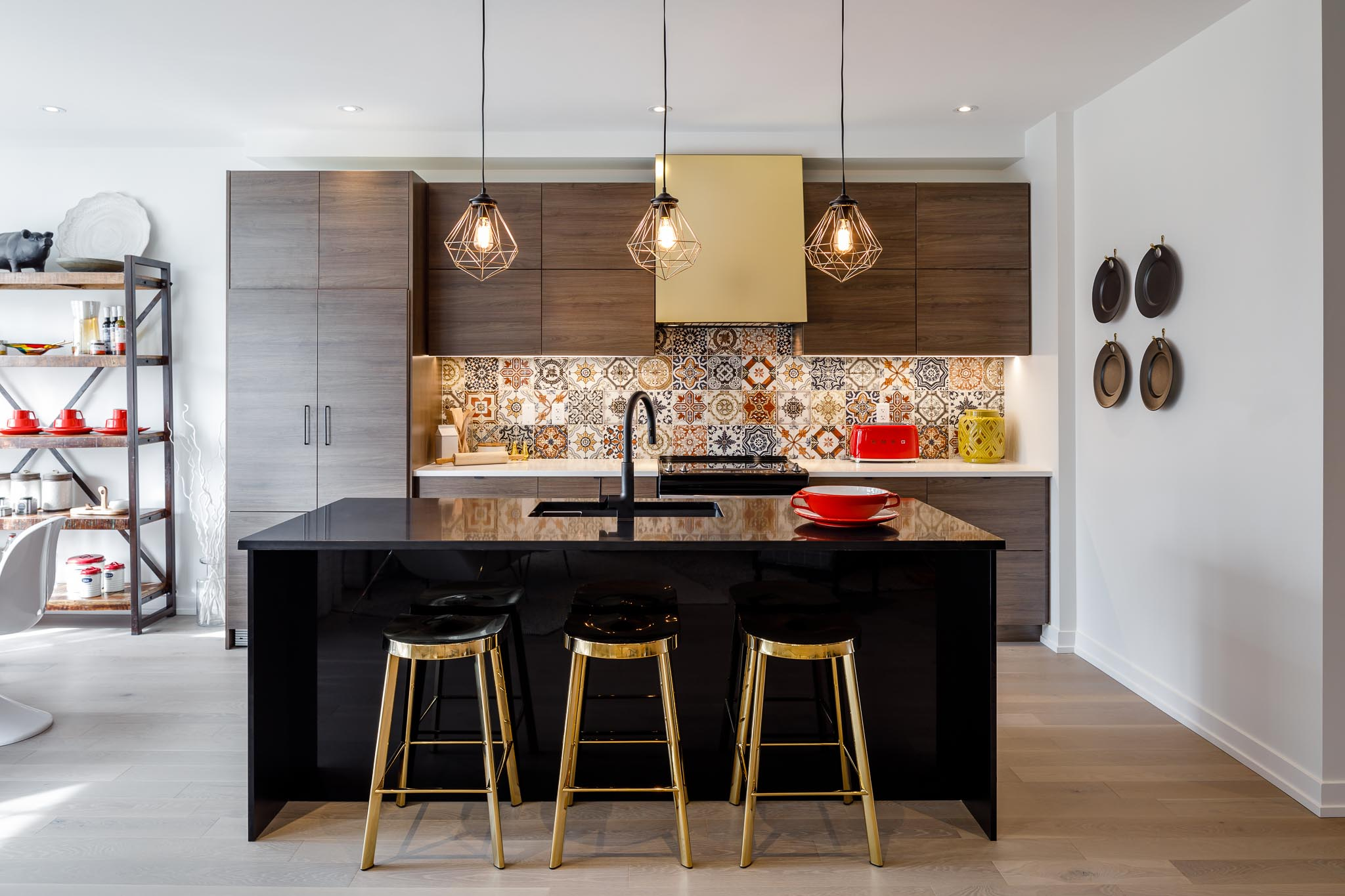 Great Gulf Westfield kitchen with black marble island, brass stools, brown cabinets, and patterned backsplash
