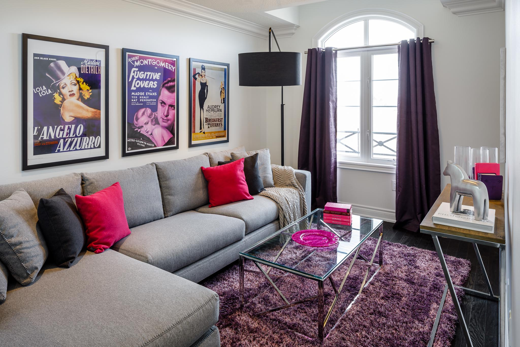 Great Gulf Westfield family room with large movie posters, purple rug, and grey sectional