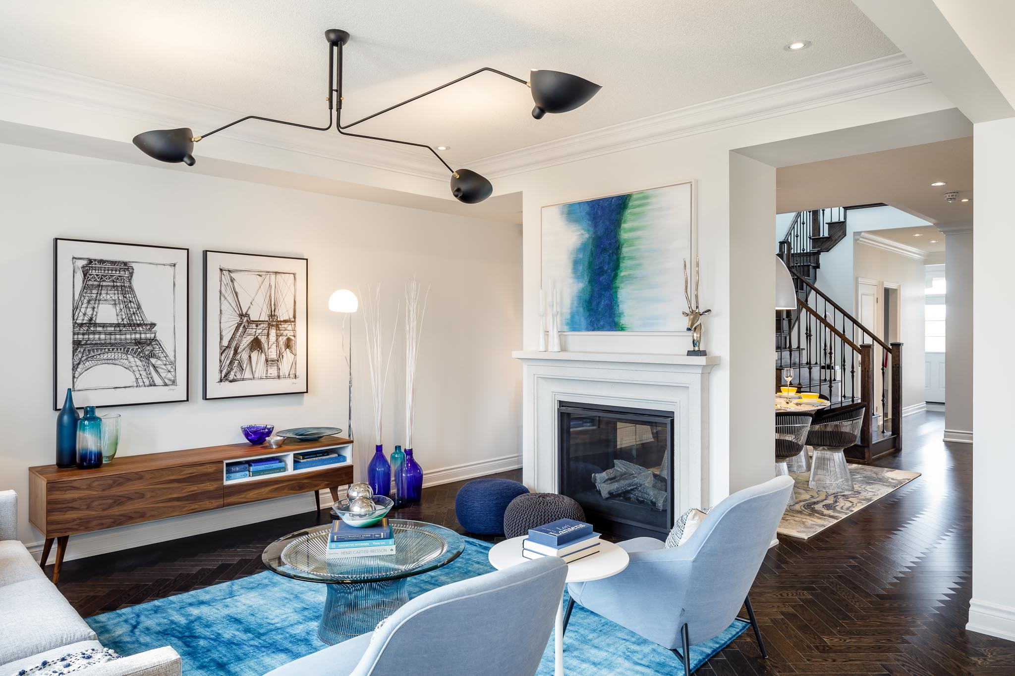 Great Gulf Westfield living room with blue rug, chairs, and artwork, and wood console table