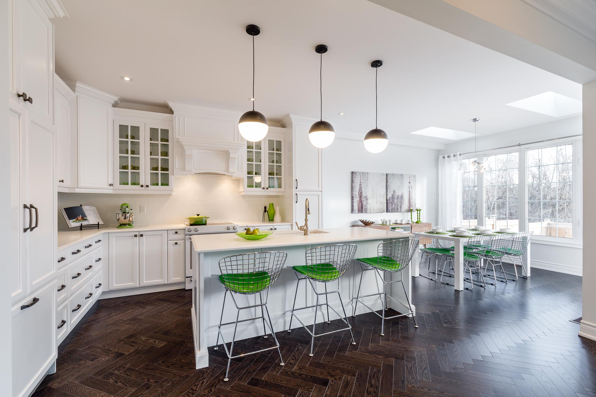 Great Gulf Westfield white kitchen with dark wood floors and metal stools with green seats