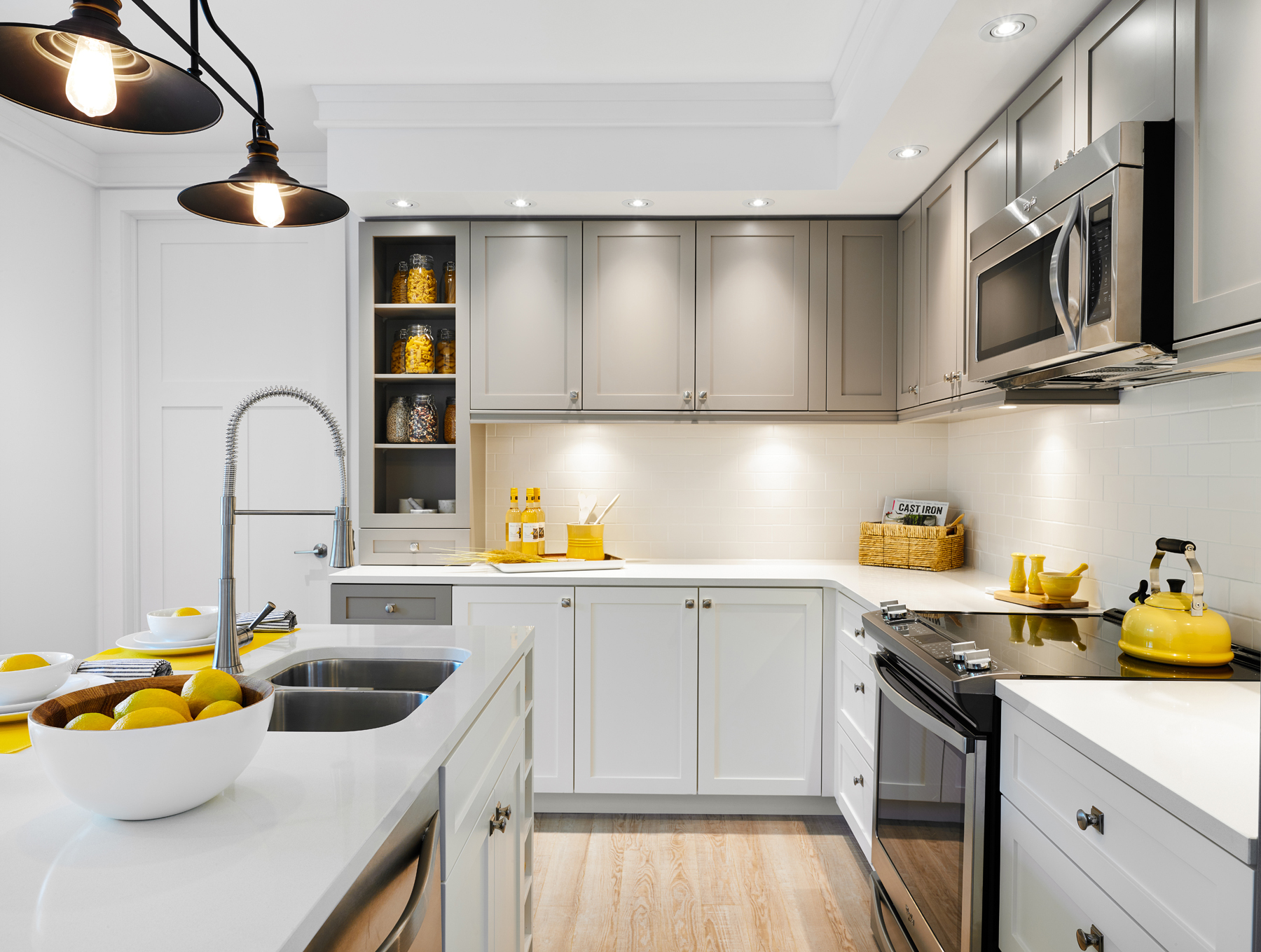 Seasons on Little Lake white and light grey kitchen with lemons, yellow tea kettle, and other yellow accessories