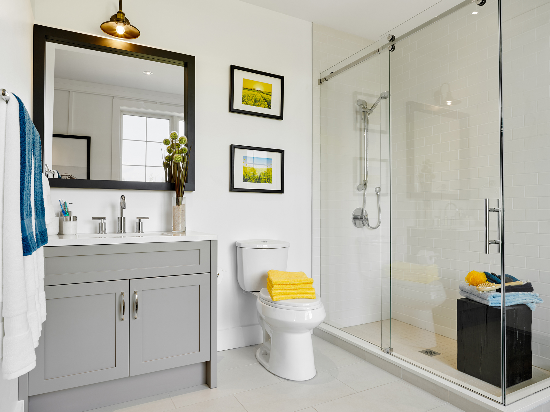 Seasons on Little Lake white bathroom with dove grey vanity, glass shower, and yellow accents
