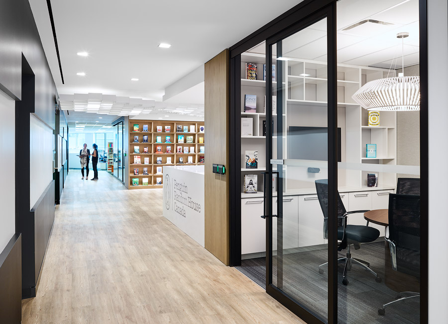 Penguin Random House hallway with wood floors and meeting room with black metal framed glass wall