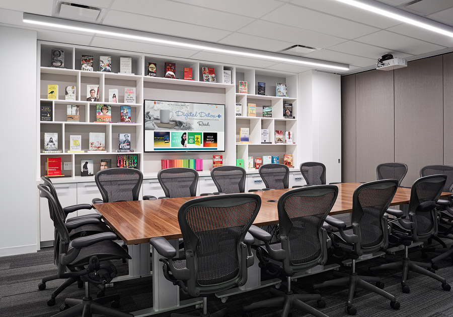Penguin Random House meeting room with large wood conference table and wall of built in bookshelves