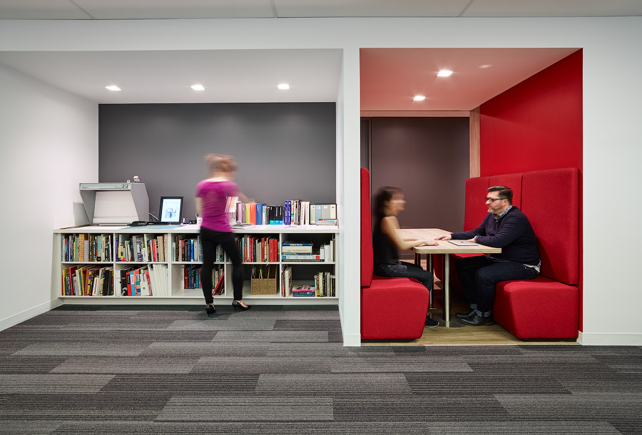 Penguin Random House booth with red walls and seating next to open area with low bookshelf