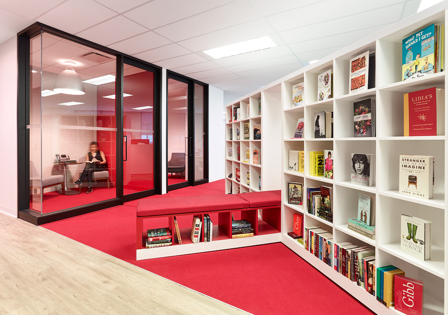 Penguin Random House reading area with red carpeting, bookshelves, and upholstered bench in front of meeting room