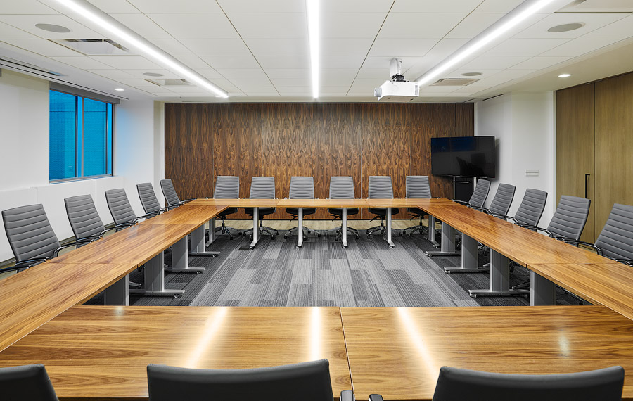 Penguin Random House boardroom with large wood table and wood paneling on walls
