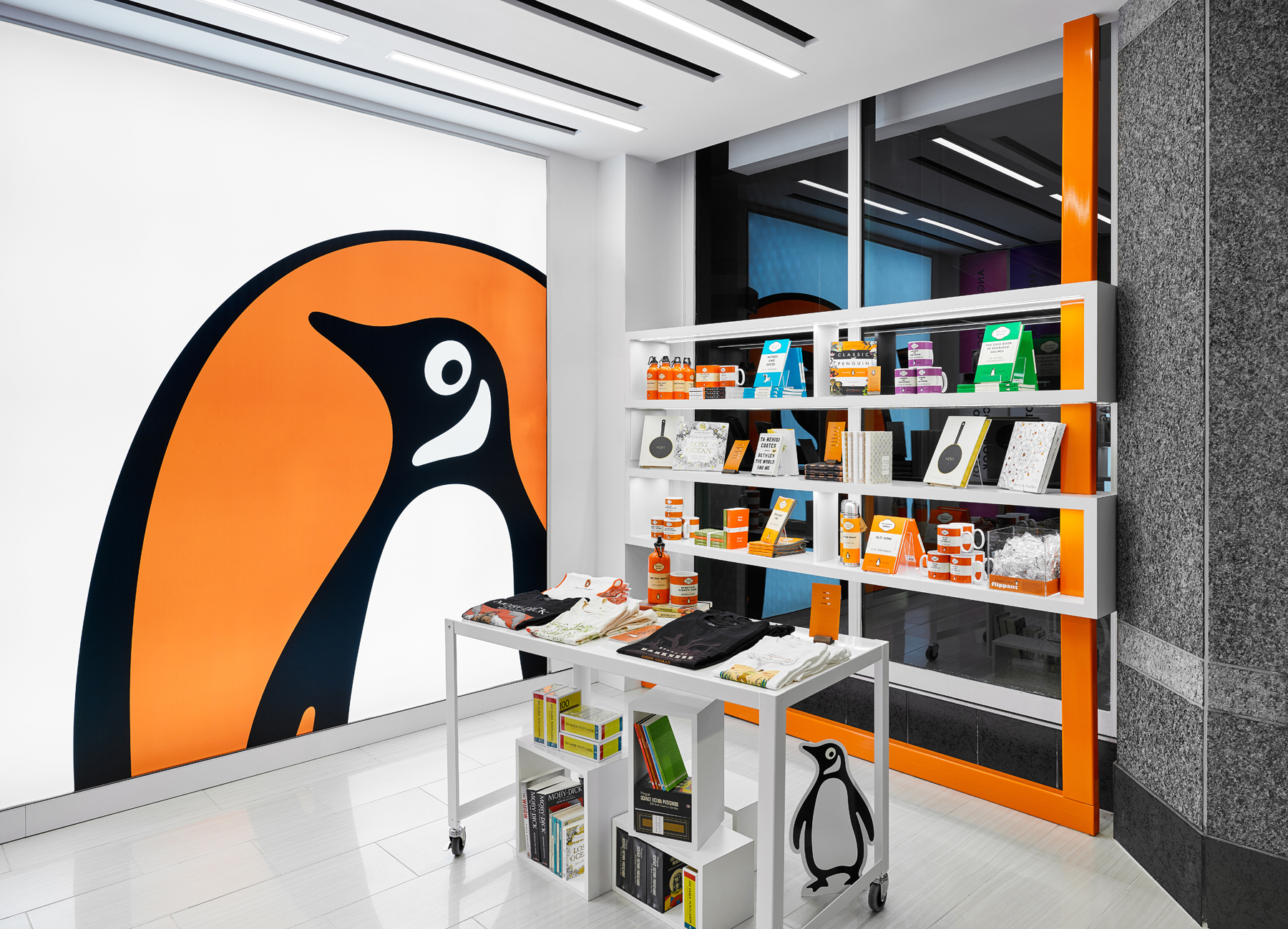Penguin Shop logo wall next to shelving and tables displaying books and Penguin merchandise