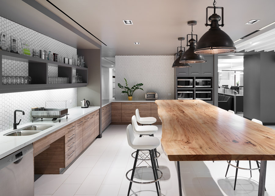 Scalar kitchen with wood slab island, wood and grey cabinets, and white hexagon tile backsplash