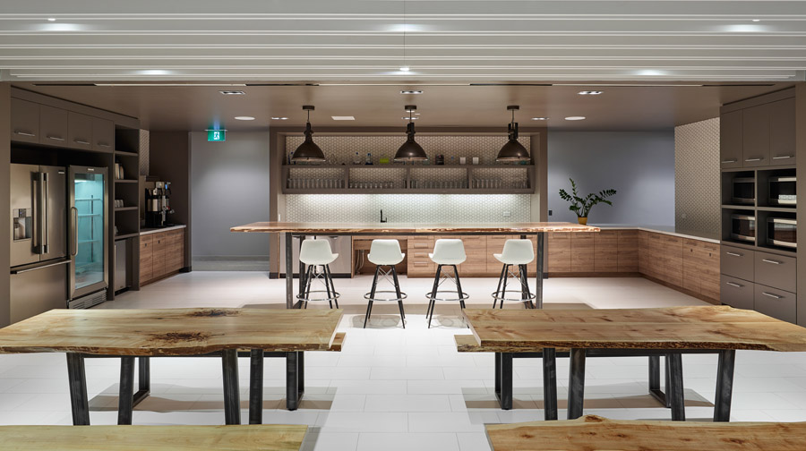 Scalar kitchen with wood tables, wood and grey cabinets, centre island, and black metal industrial pendant lights